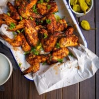 platter of spice rubbed buttermilk brined chicken wings with peppercinis on the side and ranch dipping sauce